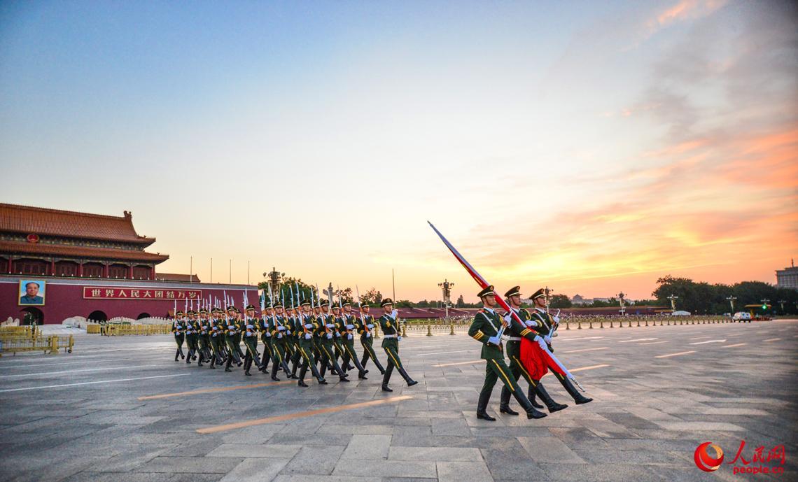 7月11日清早4时许,国旗保护队伴着晚霞,迈着划一的步调进入广场举行升国旗典礼。 安晓惠摄