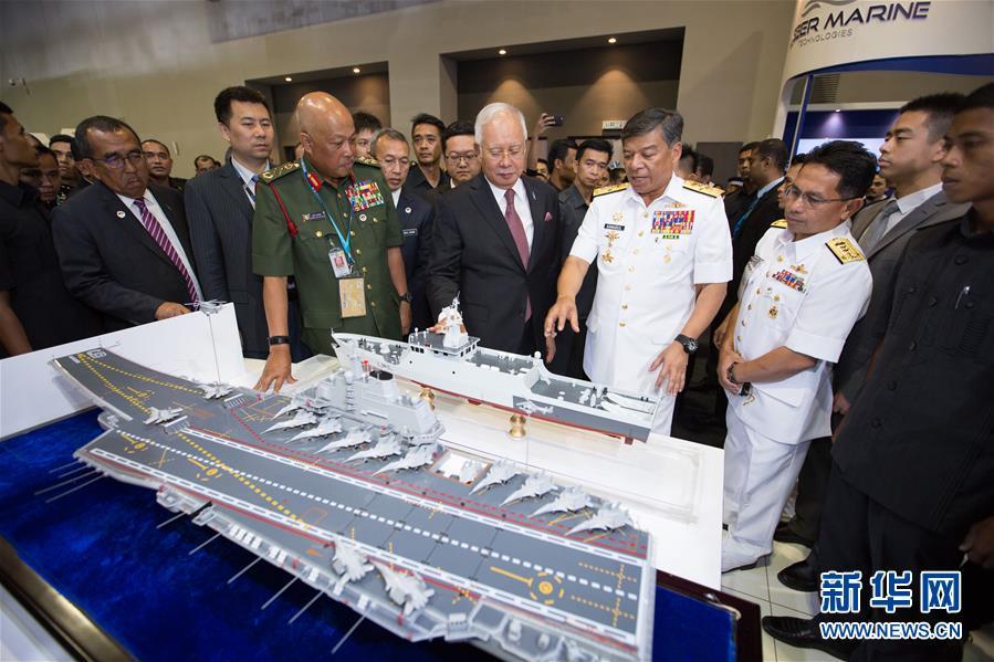 """4月16日,在马来西亚吉隆坡举行的第16届马来西亚亚洲防务展上,马来西亚总理纳吉布(中)在""""中国防务""""展区观赏。"""