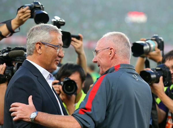 (左)与上海上港队主教练埃里克森在赛前相互致意