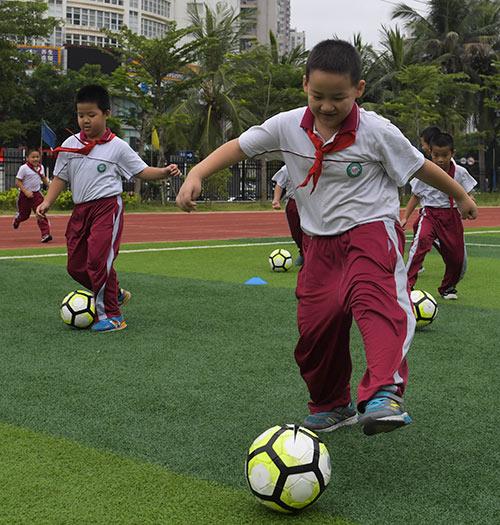 当日,海口巴塞罗那足球学校的教练来到海口市玉沙实验学校,带领学生