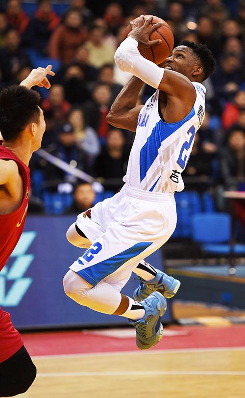 1月10日,青岛国信双星队球员吉布森(右)在比赛中投篮。摄影:新华社记者 李紫恒