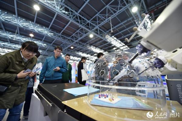 10月10日,在2018年全国双创周北京会场,观众正在认真观察腔镜机器人的操作。(人民网记者 翁奇羽)