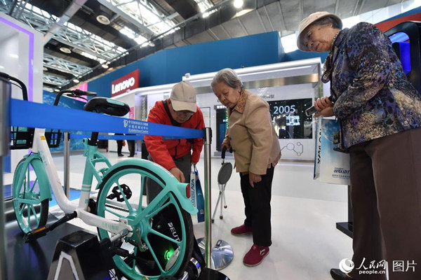 10月10日,在2018年全国双创周北京会场,,几位老人正对共享单车的联动系统进行研究。(人民网记者 翁奇羽)