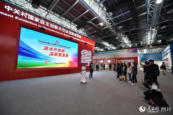 10月10日,2018年全国双创周北京会场,人工智能机器人现场秀舞技,引来参观者驻足拍摄。(人民网记者 翁奇羽)