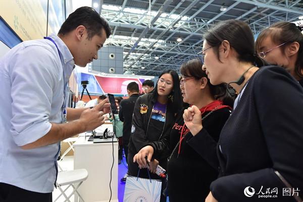"""10月10日,在2018年全国双创周北京会场,参观者现场使用空气拨片体验""""弹吉他""""带来的乐趣。(人民网记者 翁奇羽)"""