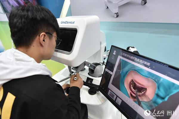 10月10日,在2018年全国双创周北京会场,观众正在操作虚拟现实医学手术模拟器体验牙科手术。(人民网记者 翁奇羽)