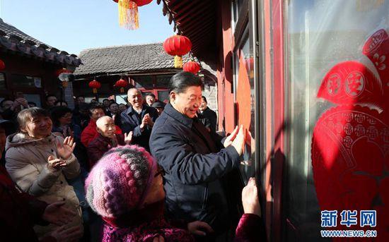 """2月1日,中共中央总书记、国家主席、中央军委主席习近平在北京看望慰问基层干部群众,考察北京冬奥会、冬残奥会筹办工作。这是1日上午,习近平在前门东区草厂四条胡同32号院,高兴地拿起一幅""""福""""字,亲自贴到门上,给这里的老街坊们拜年。 新华社记者 鞠鹏 摄"""