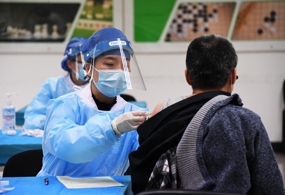 1月11日,在北京市海淀区学院路街道的一处临时新冠疫苗接种点,医务人员为接种人员接种新冠疫苗。新华社记者 任超 摄