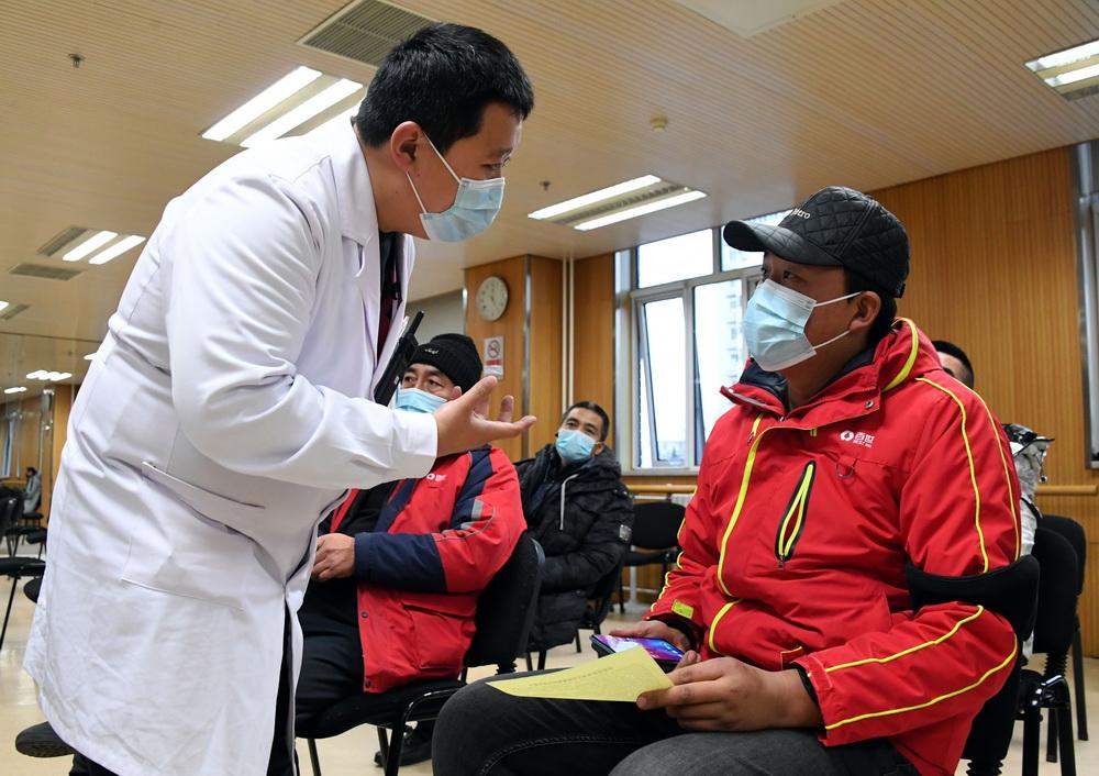 1月11日,在北京市海淀区学院路街道的一处临时新冠疫苗接种点,医务人员了解留观区人员在接种疫苗后的身体情况。新华社记者 任超 摄