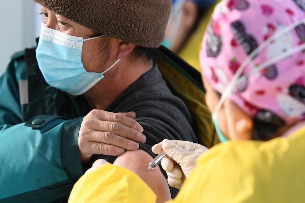 在北京市海淀区中关村街道临时集中接种点,医务人员为接种人员注射新冠疫苗(1月6日摄)。新华社记者 鞠焕宗 摄