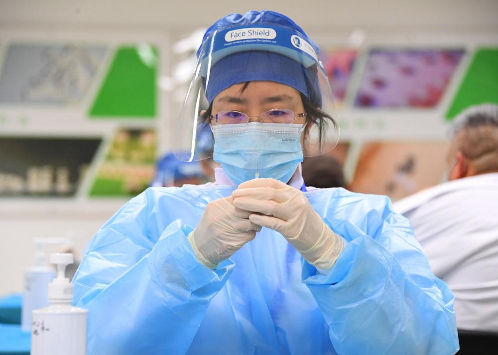 1月11日,在北京市海淀区学院路街道的一处临时新冠疫苗接种点,医务人员准备为接种人员接种。新华社记者 任超 摄